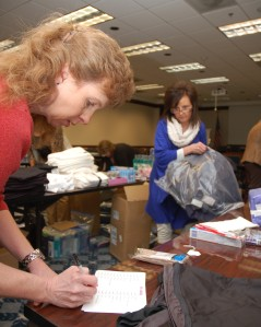 Lynn Elvis, an HEC WIRE member waits for items to be checked off the list for the back she's packing.